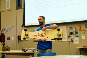"""YAA President Billy Gerchick introduces """"Eight Stages of Authorship"""" with his longboard."""
